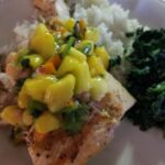 Grilled Salmon with Mango Salsa plated with rice and chopped spinach