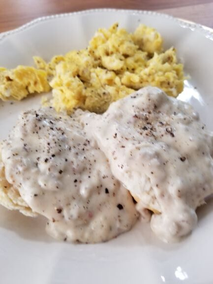 Reduce Fat Sausage Gravy and Biscuits plated with scrambled eggs