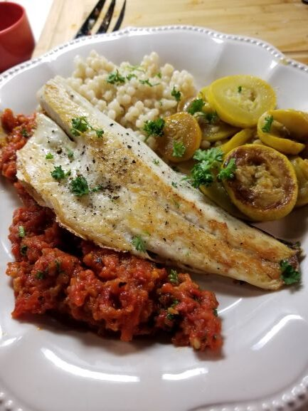 Sea Bass with Red Pepper Relish & Garlic Mayo plated with sauteéd yellow squash and israili couscous