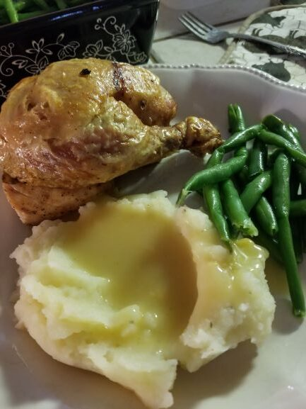 Garlic Thyme Roasted Chicken plated with mashed potatoes, chicken gravy, and steamed green beans